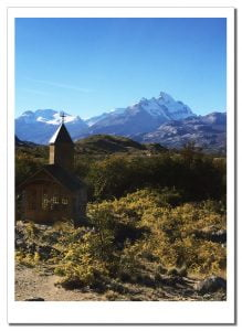 A tiny church standing in the afternoon sunshine with a distant glacial backdrop, Estancia Christina, Patagonia, Argentina