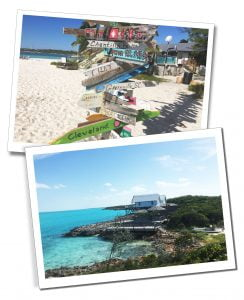 Views of a painted wooden sign pointing in numerous directions on the beach & a lodge on stilts by the shore Great Exuma, Bahamas, Caribbean