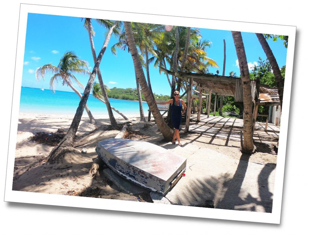SuewhereWhyWhat next to an upturned boat on the beach in Antigua, Caribbean