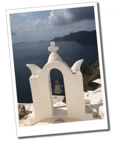 A Bell attached to a white facade, over the beautiful panorama of Santorini