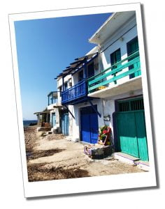 The beautiful multi coloured frontages of the tiny cottages that skirt the shoreline at Klima on the coast of Milos