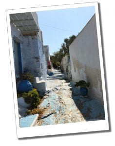 A view of in Plaka, Milos of a backstreet scene with rustic pots and blue and white walls
