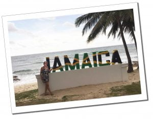 SueWhereWhyWhat on the beach with a large Black, yellow & green sign spelling out the word Jamaica