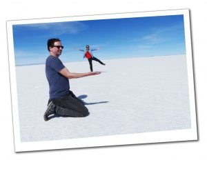 SueWherewhywhat pretends to balance on a mans hand on the Uyuni Salt flats in Bolivia with her arms and legs outstretched