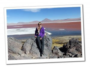 SueWhereWhyWhat sits in front of the pink lake with flamingoes at Laguna Colorada, Bolivia