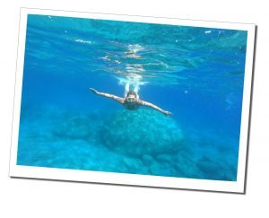 Swimming underwater during Milos boat tour, Greece