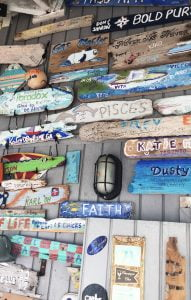 A wall full of Wooden signs and messages at Compass Cay, Exumas