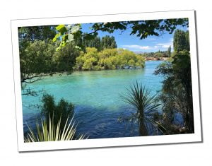 Azure waters viewed from the leafy river bank at Wanaka, New Zealand